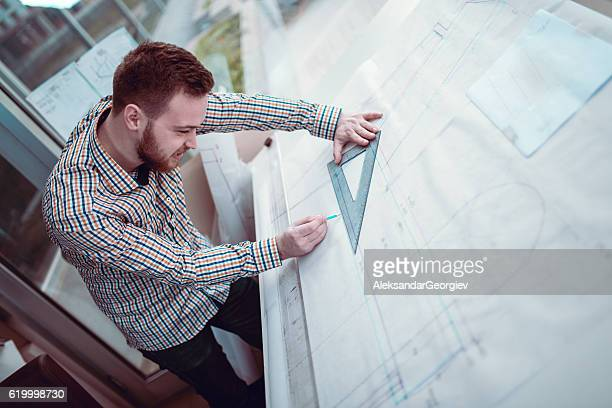 Young Architect Designer Working Blueprint Plans in His Office