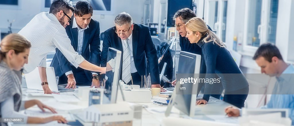 Young architect explaining project plan to clients : Stock Photo