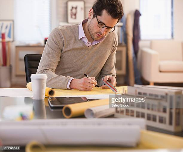 Jeune architecte qui passe au-dessus de plans