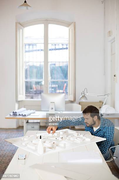 Young architect making architectural model