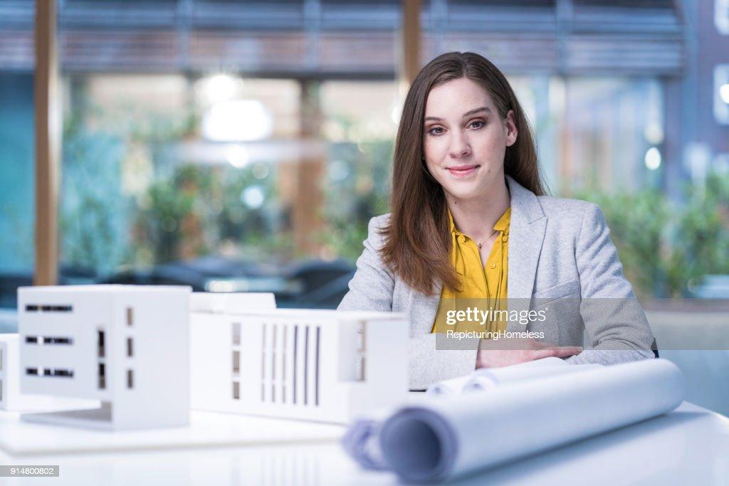 Architektin sitzt hinter ihrem Modell und schaut in die Kamera : Stock-Foto