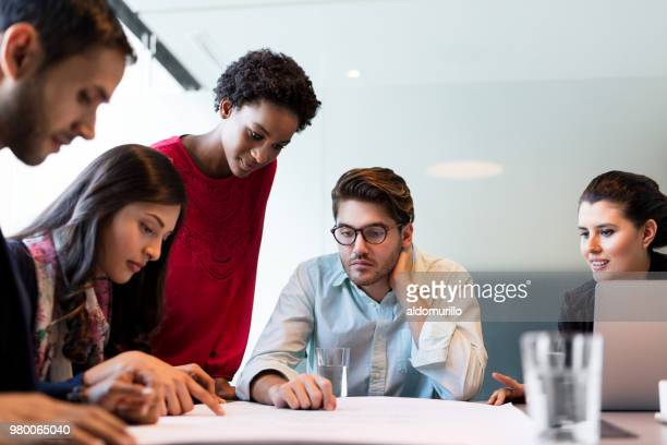 Young architects checking floor plan together