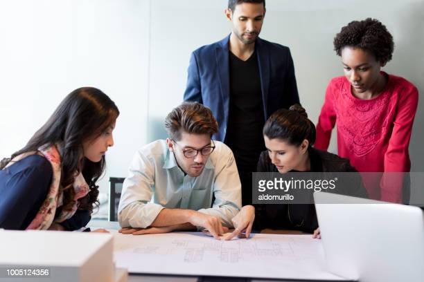 jeunes architectes vérifier carte sol - plan moyen angle de prise de vue photos et images de collection