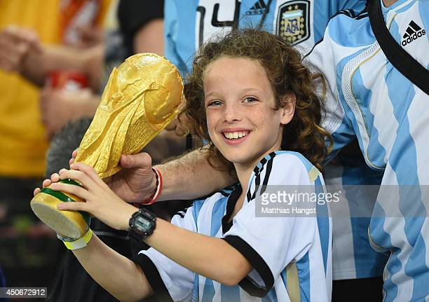 A young Argentina fan holds a replica of the World Cup trophy during the 2014 FIFA World Cup Brazil Group F match between Argentina and...