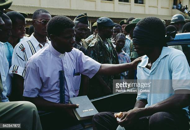A young Armed Forces of Liberia soldier accused of looting and murder receives some final Biblical words from a pastor before being led away to face...