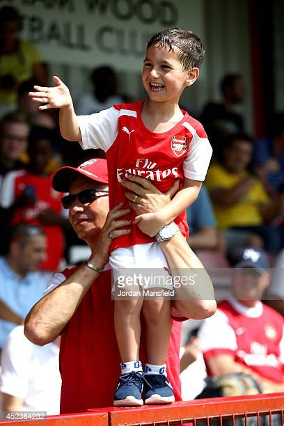 A young Arsenal fan waves as Arsenal manager Arsene Wenger walks onto the pitch ahead of the pre season friendly match between Borehamwood and...