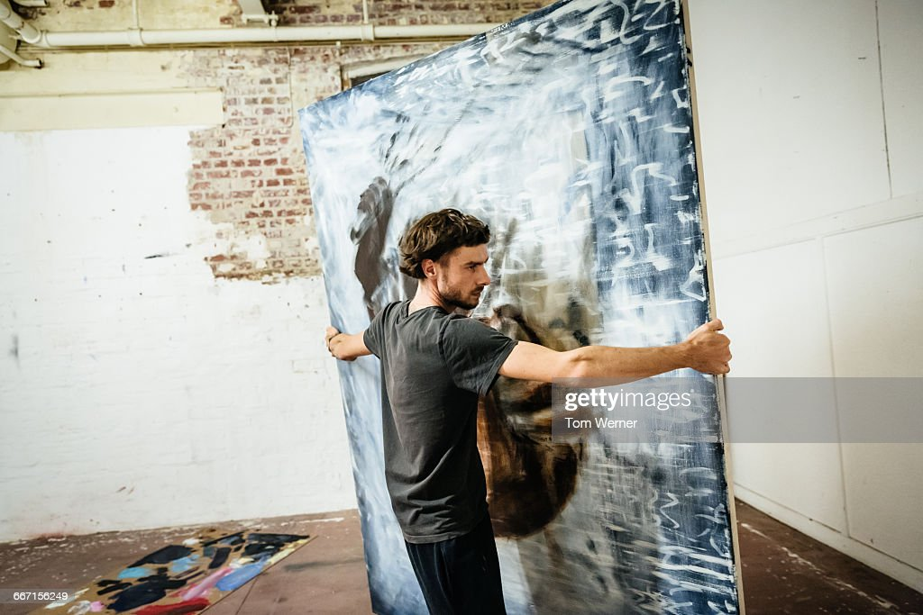 Young artist carrying big painting : Stock Photo