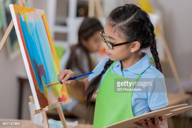 Young artist concentrates while painting