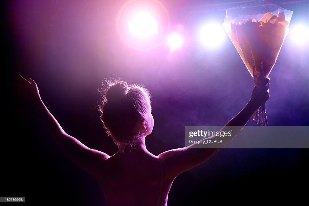 Young artist girl greeting her public after performance on stage : Stock Photo