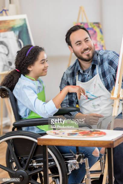 Young artist in wheelchair takes art lesson