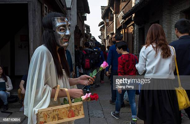 WUZHEN TONGXIANG ZHEJIANG CHINA A young artist is acting an experimental drama and making interactives with the tourists on the ancient street The...