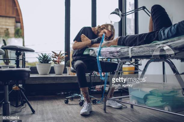 young artist making tattoo - tattooing stock photos and pictures