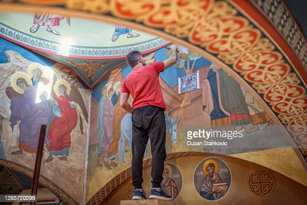 young artist painting an orthodox church walls with a brush - monument stock pictures, royalty-free photos & images
