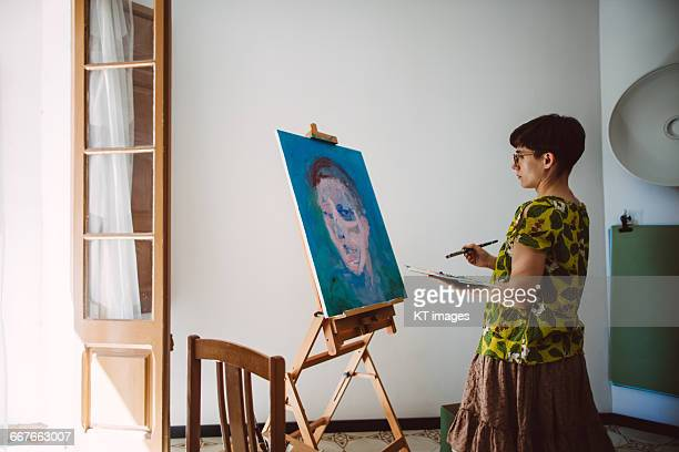 young artist painting at home studio - painting stock pictures, royalty-free photos & images