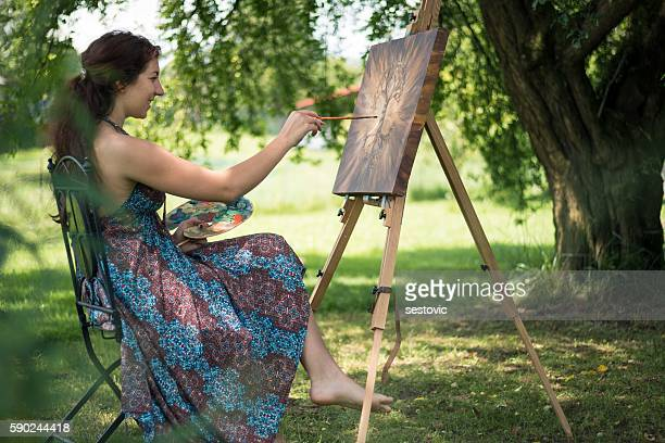 Young artist painting outside in nature
