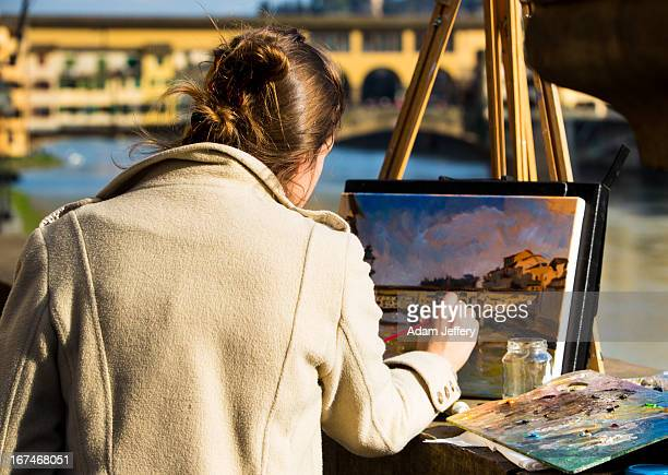 Young artist paints the Ponte Vecchio in the late afternoon sun in Florence, Italy on March 15, 2013.