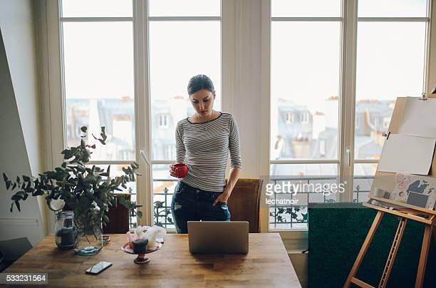 若いアーティストの女性彼女のパリのアパートメント