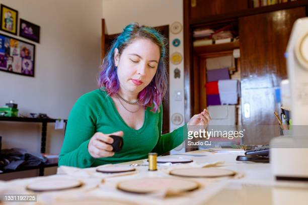 young artist working on her embroidery hoop design by selecting thread colors - art and craft product stock pictures, royalty-free photos & images