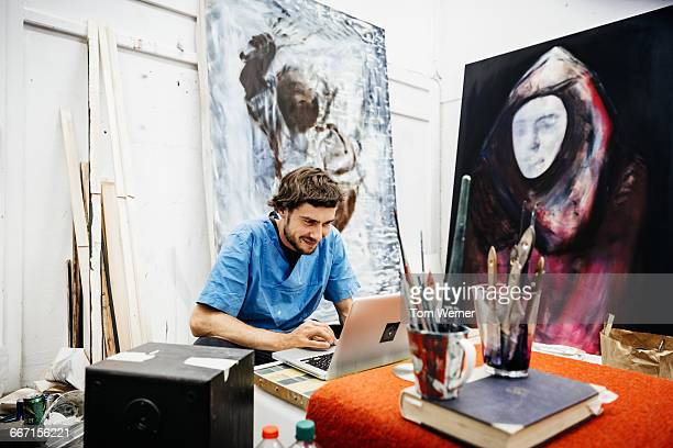 Young artist working on laptop in atelier