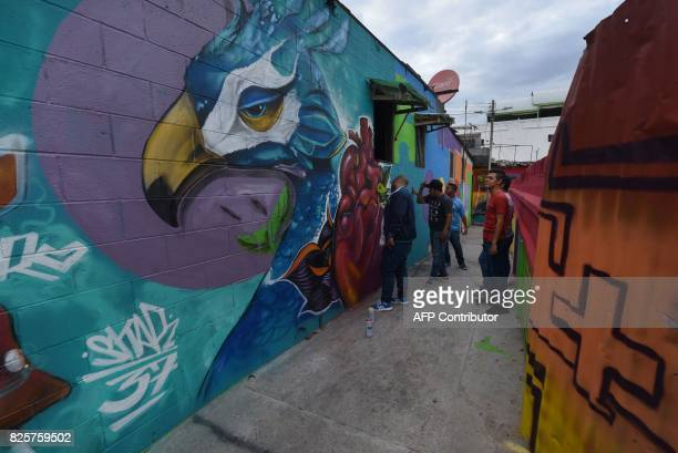 Young artists make a graffiti at Santa Fe Community in San Salvador on July 18 2017 A group of young people with the support of San Salvador's...