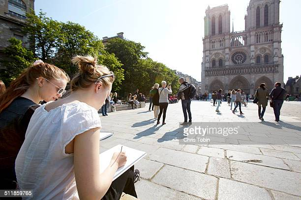 Young artists sketching Notre Dame Paris