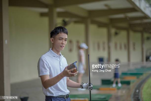 young asia chinese man holding his broken driver in his golf course lesson during rainy day. - individual event stock pictures, royalty-free photos & images