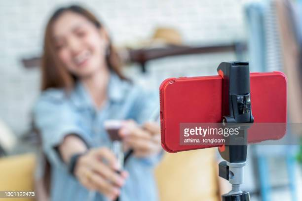 young asia girl online by live streaming. selling it online live streaming concept.focus on mobile phone. - young animal stock pictures, royalty-free photos & images
