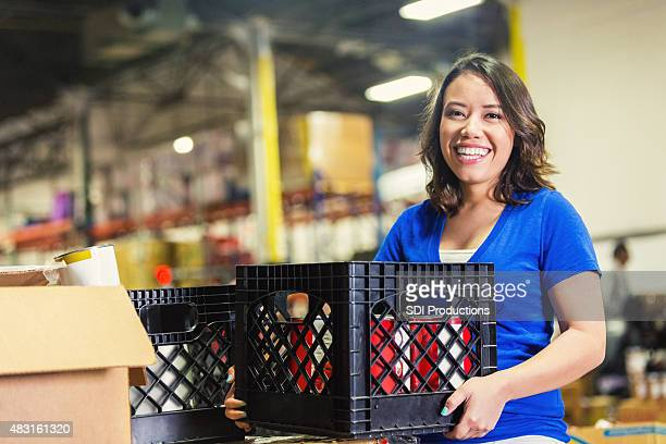young asian american volunteer working in food bank warehouse - charitable donation stock pictures, royalty-free photos & images