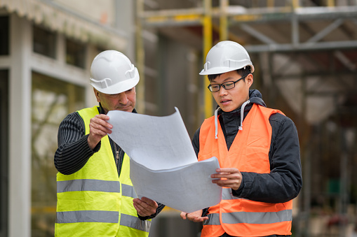 Young Asian apprentice at work on construction site with senior engineer. Outdoors 878440230
