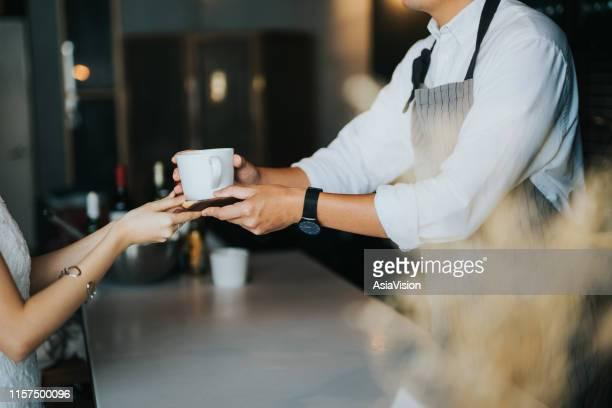 junge asiatische barista übergibt einen kaffee an weibliche kundin über die café-bar im café - geben stock-fotos und bilder