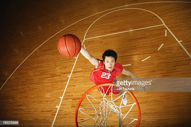 Young Asian basketball player aiming for the net