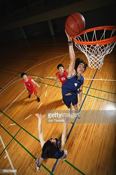 Young Asian basketball player making a dunk