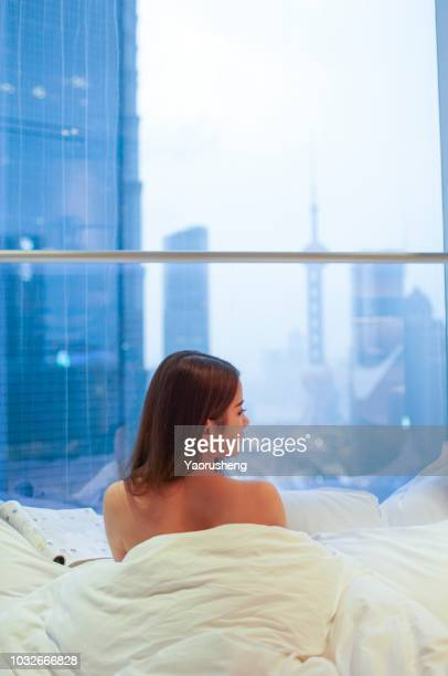 young asian beautiful woman wearing dress gown looking through floor window - nake woman stock photos and pictures