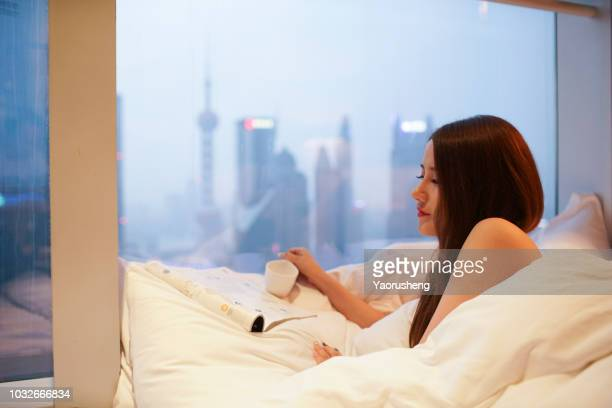 young asian beautiful woman wearing dress gown looking through floor window - woman nake stock photos and pictures