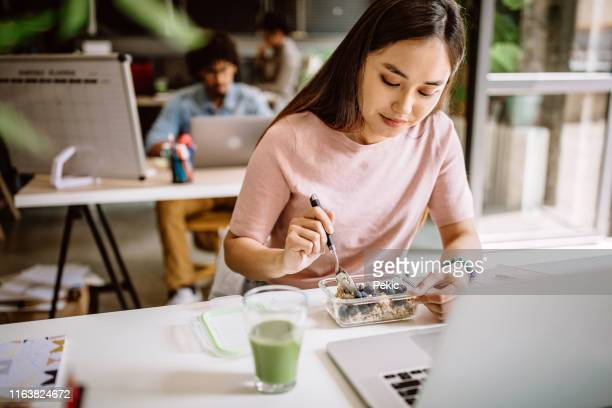 young asian blogger having vegetarian breakfast at work - snack stock pictures, royalty-free photos & images