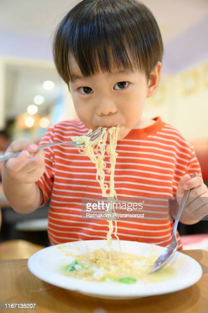young asian boy eat noodle and look at camera - noodles stock pictures, royalty-free photos & images