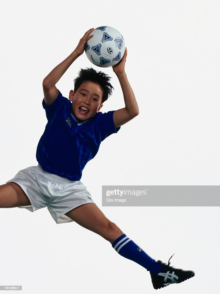 Young Asian boy holding football, jumping in mid-air : Stock Photo