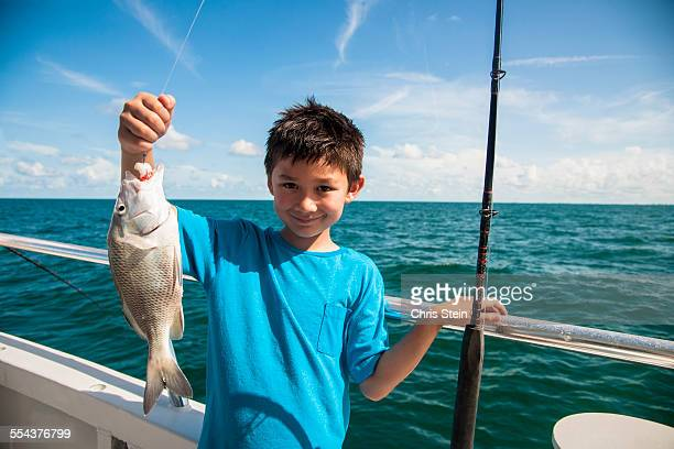 Young Asian Boy holding up the fish he just caught