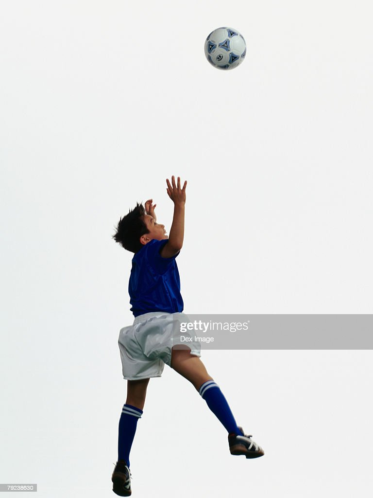 Young Asian boy jumping to head soccer ball in mid-air : Stock Photo