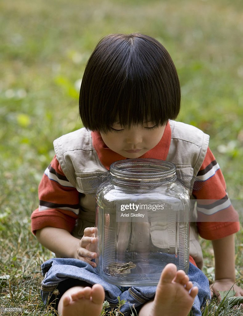 Young Asian Boy Looking at Frog in Jar : Stock Photo