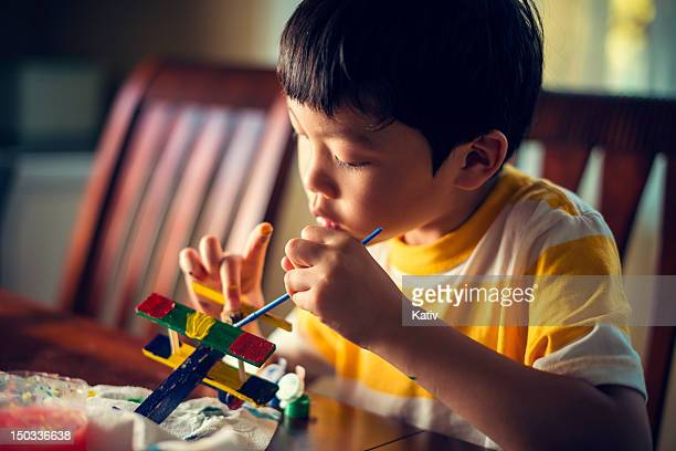Young Asian Boy Painting a Wooden Airplane