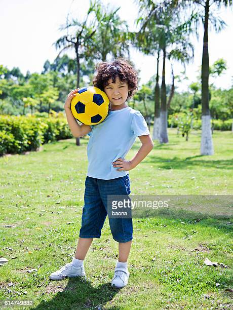 Young asian boy playing football in park