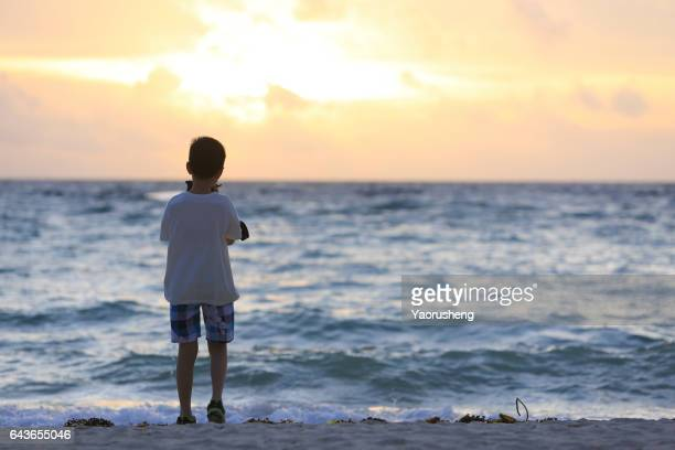 Young Asian boy taking the photo for sunset at the beach