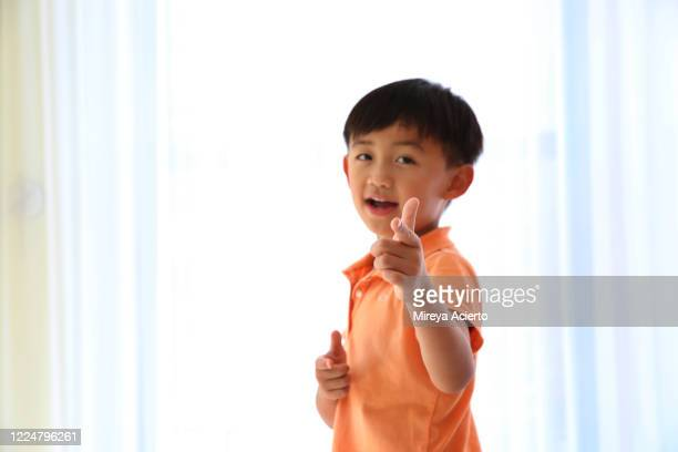 a young asian boy with an orange shirt, smiles and points is finger in a brightly lit room. - オレンジ色のシャツ ストックフォトと画像