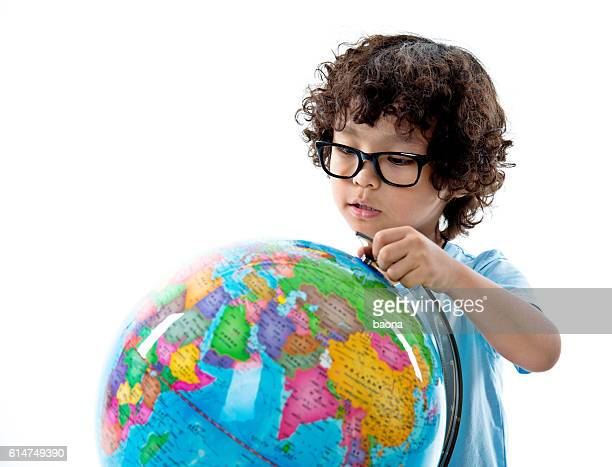 Young asian boy with globe against white background