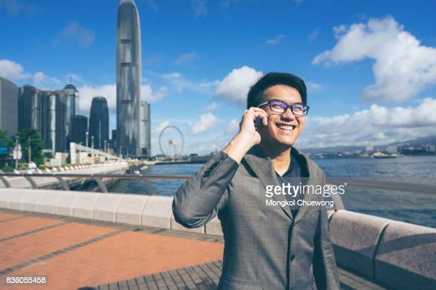 Young asian business handsome smiling while using his smartphone