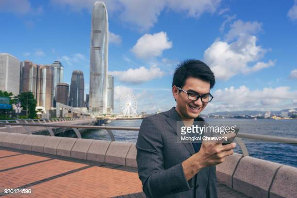 Young asian business handsome smiling while using his smartphone.