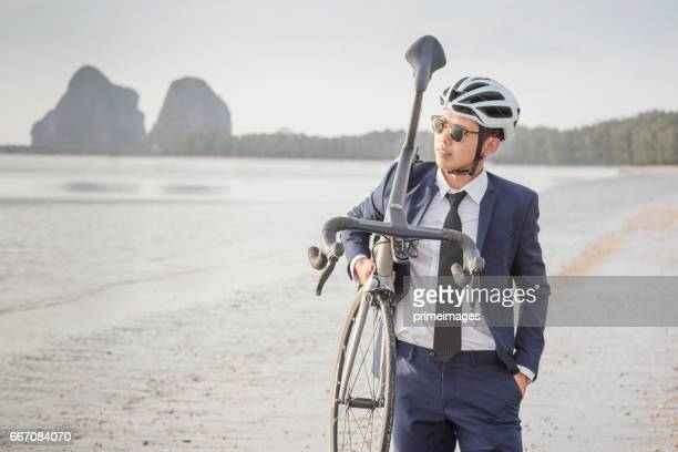 Jonge Aziatische zakenman fietstocht het strand ontspannen bij de zonsondergang