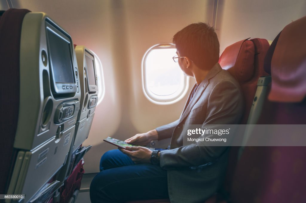 Young asian business man smiling and looking view at window in airplane : Stock Photo