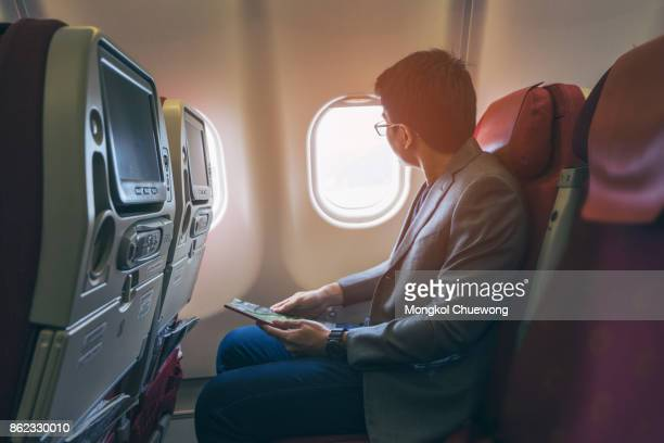 Young asian business man smiling and looking view at window in airplane